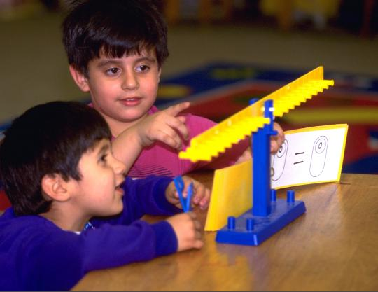 Young children discovering equals means balanced on a math balance