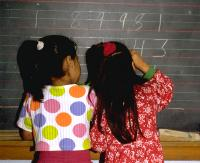 Grade 1 bilingual Hispanic girls adding a long column of 5-digit numbers
