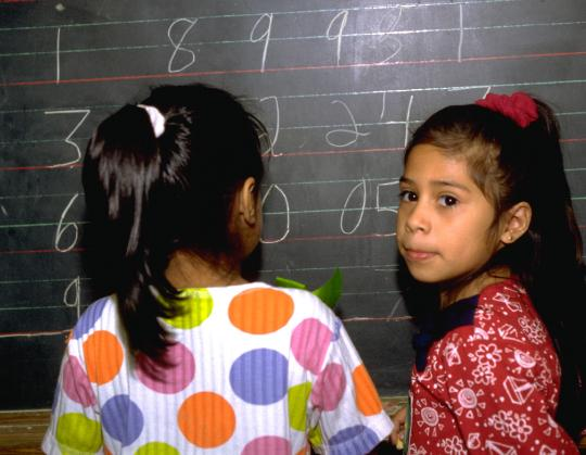 Elementary school bilingual Hispanic children adding big numbers on a chalkboard